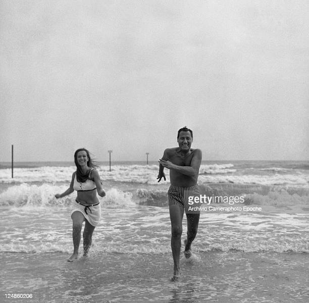 Italian actor Alberto Sordi, wearing a striped swimmin suit, portrayed while running out of the sea with the actress Daniela Surina, Lido, Venice,...