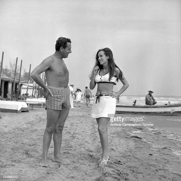 Italian actor Alberto Sordi, wearing a striped swimmin suit, portrayed while talking on the beach to the actress Daniela Surina, Lido, Venice, 1967.