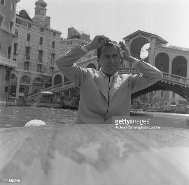 Italian actor Alberto Sordi, wearing a suit, portrayed while combing his hair on a water taxi, Rialto bridge in the background, Venice, 1959.