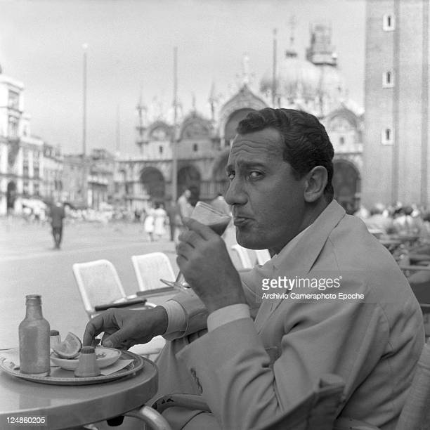 Italian actor Alberto Sordi wearing a suit portrayed while sipping a glass of tomato juice sitting on a terrace in St Mark Square salt pepper and a...