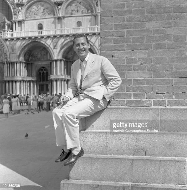 Italian actor Alberto Sordi wearing a suit portrayed while sitting on a corner of the bell tower in St Mark Square smoking a cigarette Venice 1959