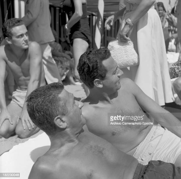 Italian actor Alberto Sordi with Paolo Stoppa lying on the Lido beach both wearing a swimming suit Lido Venice 1957