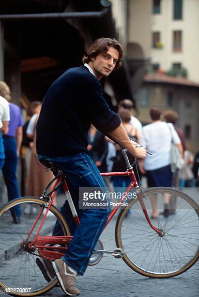 Italian actor Alessandro Preziosi riding a bike in the streets of the city centre Florence 1999