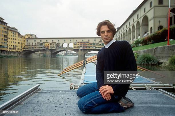 Italian actor Alessandro Preziosi sitting on a floating platform In the background the Ponte Vecchio seen from Santa Trinita Bridge Florence 1999