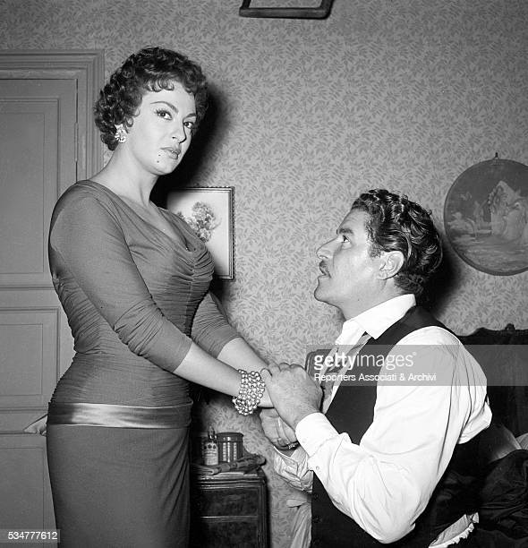Italian actor Amedeo Nazzari kneeling in front of Greekborn Italian actress Yvonne Sanson during a break on the set of the film Nobody's Children 1951