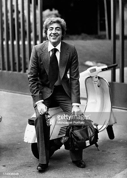 Italian actor and comedian Gino Bramieri sitting on a Vespa. Rome, 1973.