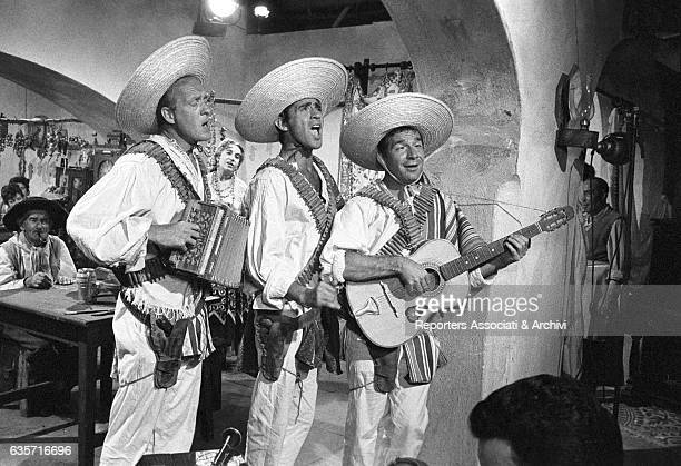 Italian actor and comedian Walter Chiari in the middle with Italian actors Ugo Tognazzi and Raimondo Vianello dressed as mariachi in a scene from the...
