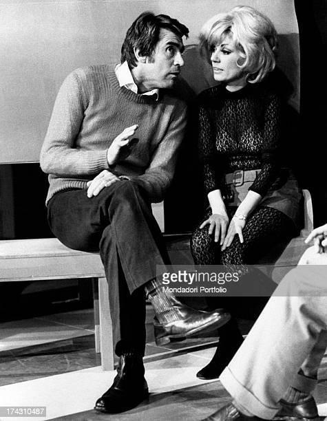 Italian actor and comedian Walter Chiari talking to Italian actress Emy Eco in Nude Look Brescia 1971
