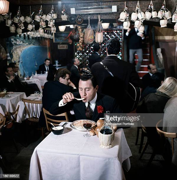 Italian actor and director Alberto Sordi eating a dish of spaghetti sitting at the table of a restaurant in the film Smoke Over London Many flasks of...