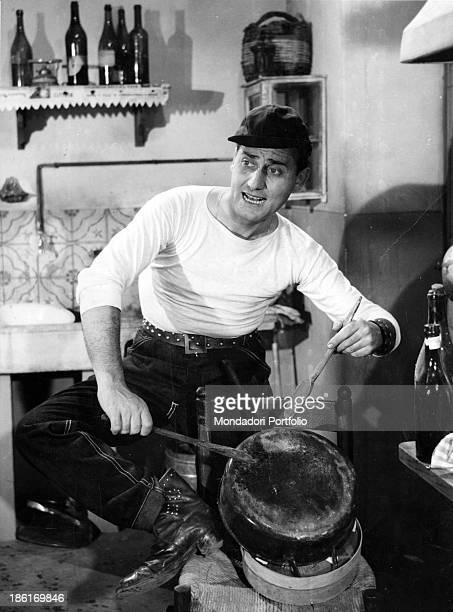 Italian actor and director Alberto Sordi playing a pan with two wooden spoons in the film An American in Rome 1954