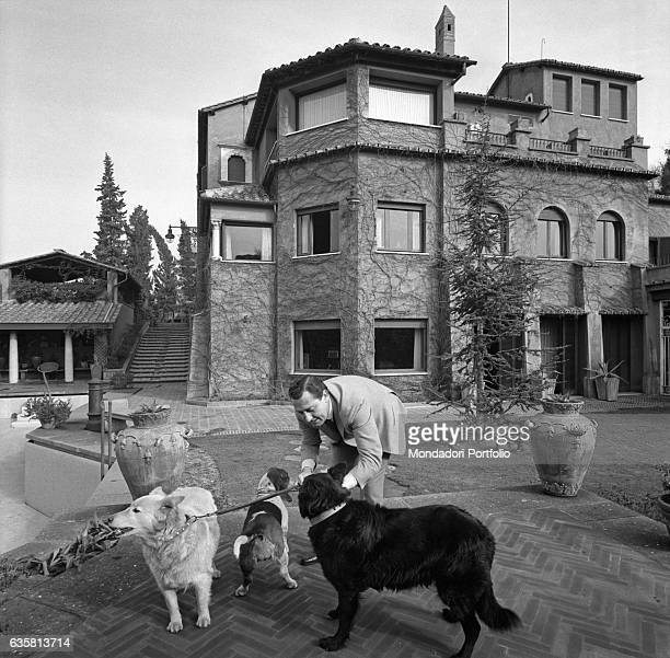 Italian actor and director Alberto Sordi playing with his three dogs in his house on via Druso nearby the Baths of Caracalla Rome 5th February 1967