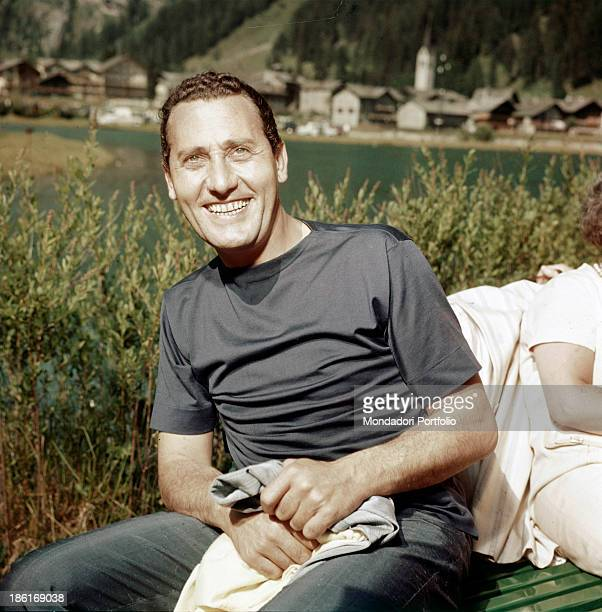 Italian actor and director Alberto Sordi smiling by a lake 1960s