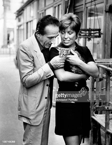 Italian actor and director Arnoldo Foà and his Italian wife Ludovica Volpe stroking a cat 1970s