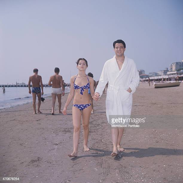 'Italian actor and director Christian De Sica walking hand in hand in a bathrobe with his partner and future film producer Silvia Verdone at the...