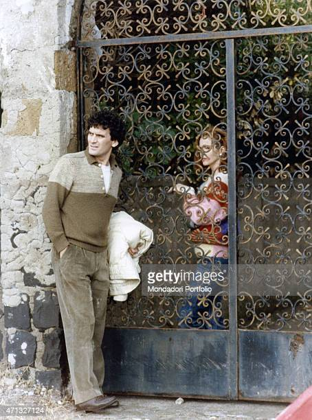 Italian actor and director Massimo Troisi and Italian actress Giuliana De Sio acting divided by a wroughtiron gate in the film Scusate il ritardo 1983