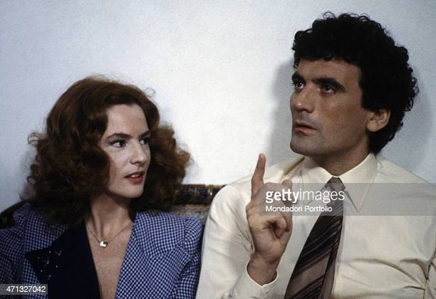 Italian actor and director Massimo Troisi gesticulating beside Italian actress Giuliana De Sio on the set of the film Scusate il ritardo 1983