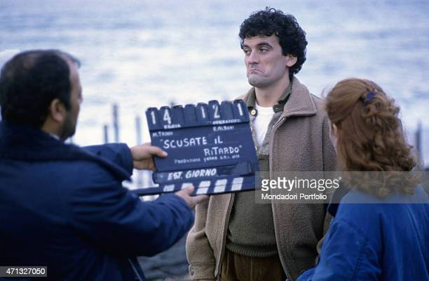 Italian actor and director Massimo Troisi grimacing beside Italian actress Giuliana De Sio on the set of the film Scusate il ritardo 1983