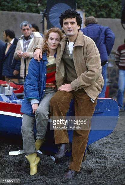 Italian actor and director Massimo Troisi hugging Italian actress Giuliana De Sio on the set of the film Scusate il ritardo. 1983