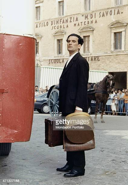 Italian actor and director Massimo Troisi posing holding some suitcases in front of the nursery school Margherita di Savoia in the film Le vie del...
