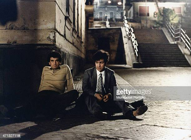 Italian actor and director Massimo Troisi sitting in the street beside Italian actor Lello Arena in the film Scusate il ritardo 1983