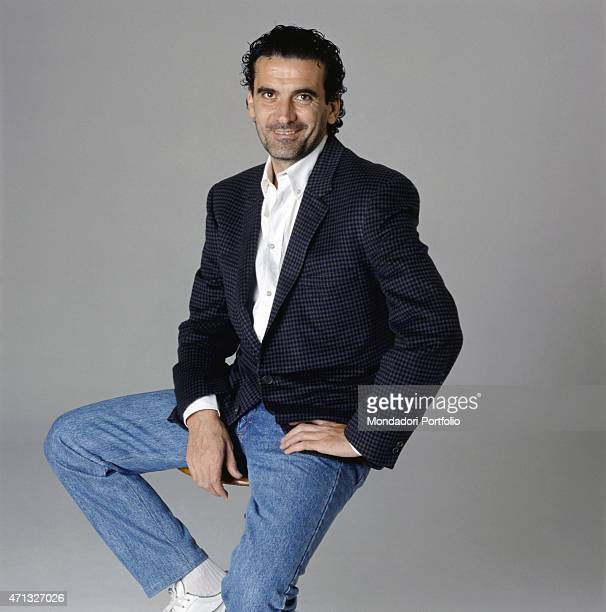Italian actor and director Massimo Troisi sitting on a stool 1989