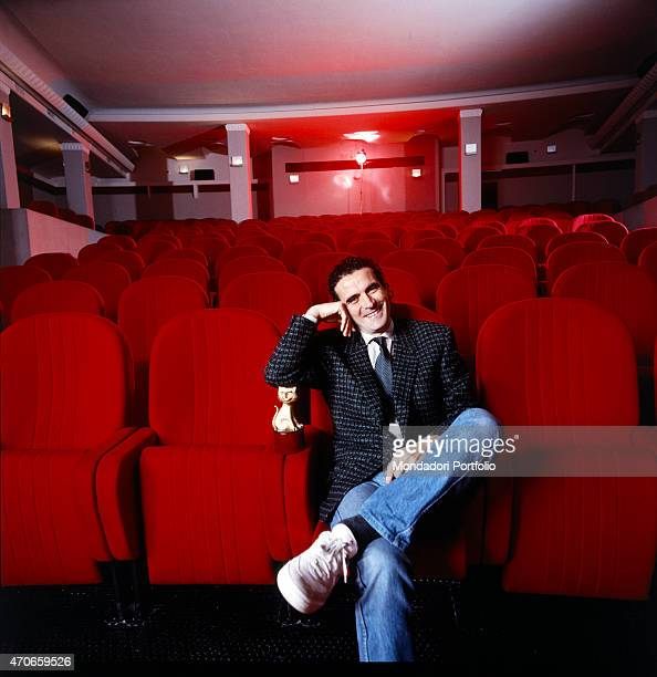 Italian actor and director Massimo Troisi smiles sitting on the front row of a little cinema hall leaning his elbow on a Telegatto a TV award Troisi...