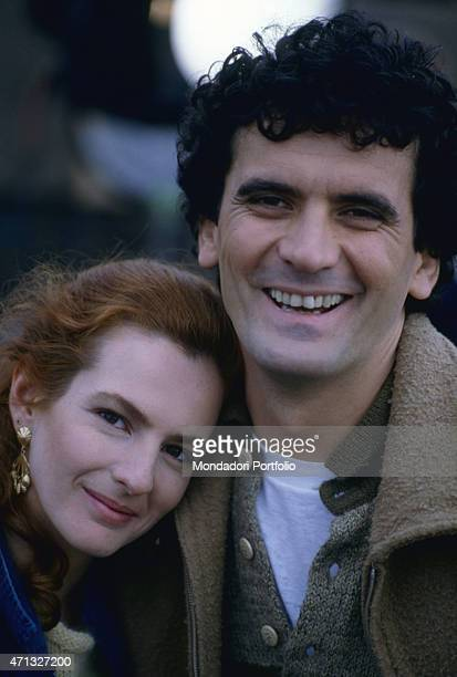 Italian actor and director Massimo Troisi smiling beside Italian actress Giuliana De Sio on the set of the film Scusate il ritardo. 1983