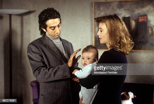 Italian actor and director Sergio Rubini cuddling the baby held by Italian actress Margherita Buy in the film Condemned to Wed Italy 1993