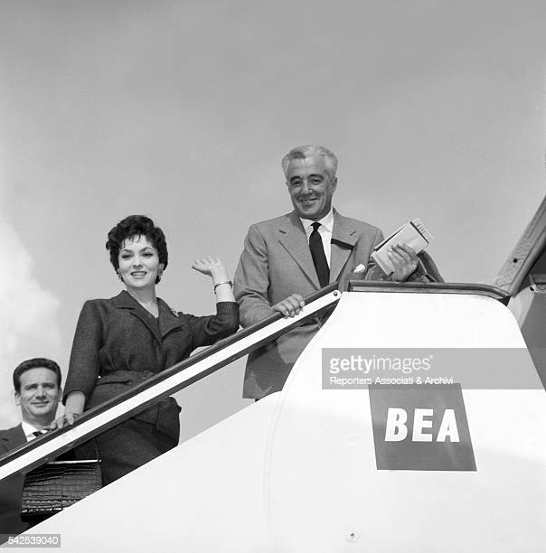Italian actor and director Vittorio De Sica and Italian actress Gina Lollobrigida waving their hands before leaving for London on a plane Ciampino...