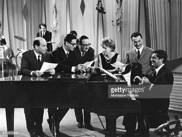Italian actor and musician Lelio Luttazzi accompanying the Quartetto Cetra at the piano beside Italian conductor Gorni Kramer The Italian vocal band...