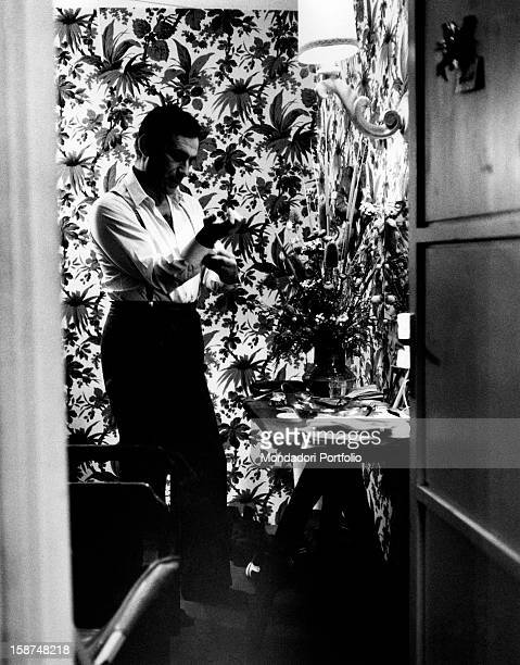 Italian actor and presenter Alberto Lupo born Alberto Zoboli buttons up a wristband in a flowerwallpapered dressing room March 1966