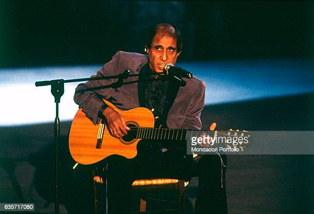 Italian actor and singer Adriano Celentano playing the guitar in the TV show Francamente me ne infischio Milan 1999