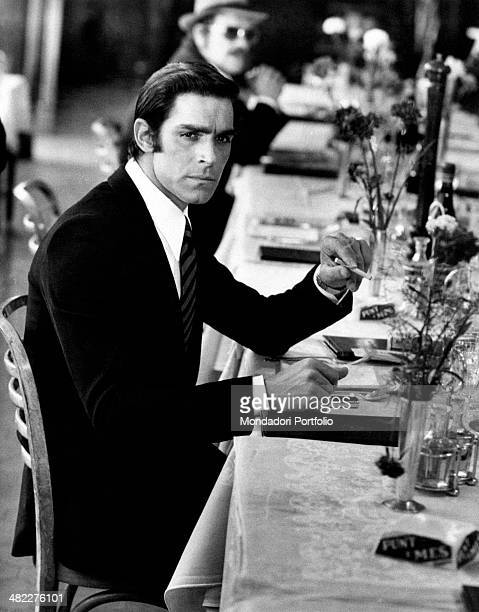 Italian actor and singer Fabio Testi and French actor Raymond Pellegrin sitting at the table of a restaurant in the film Gang War. Naples, 1972