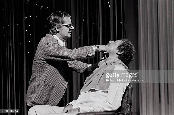 Italian actor and singer Serge Reggiani shaves American singer and composer Mort Shuman during a stage performance in Paris
