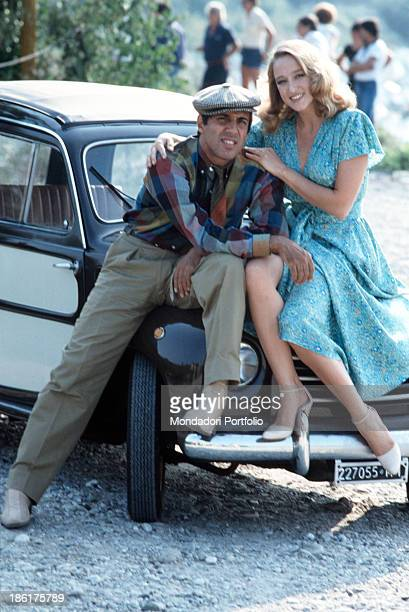 Italian actor and singer-songwriter Adriano Celentano and Italian actress Eleonora Giorgi sitting on a car bonnet on the set of the film Velvet...