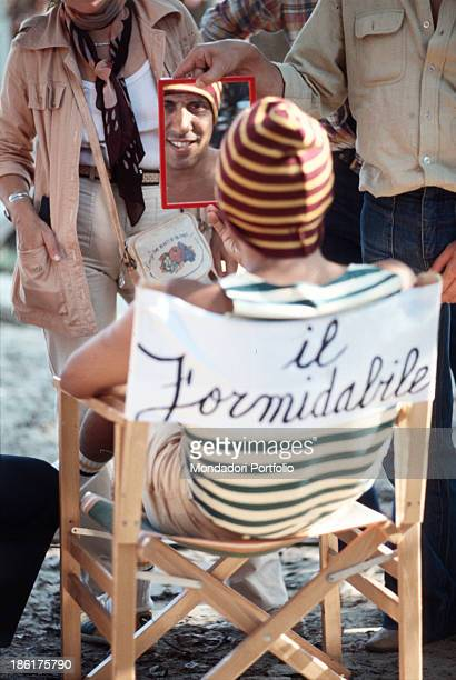 Italian actor and singersongwriter Adriano Celentano looking at himself in a mirror seated on a director's chair with the inscription Il formidabile...
