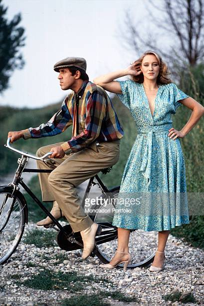 Italian actor and singer-songwriter Adriano Celentano sitting on a bicycle while Italian actress Eleonora Giorgi resting her elbow on his shoulder on...