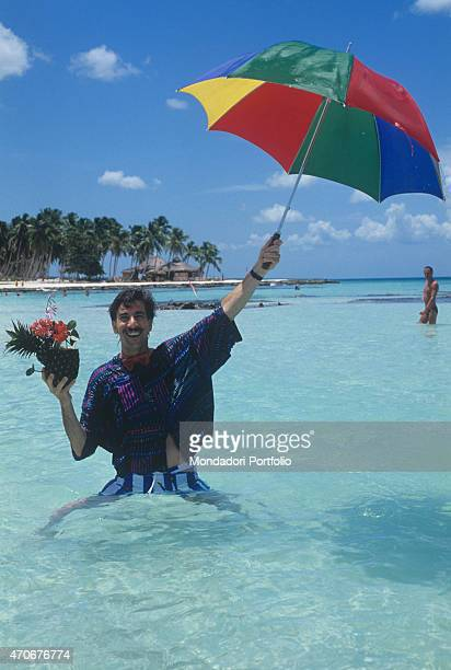 Italian actor and TV presenter Marco Columbro smiling holding a cocktail and a coloured pieces umbrella Santo Domingo 1989