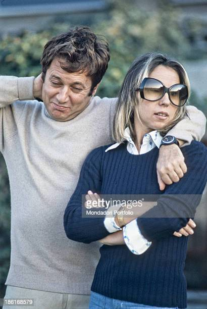 Italian actor and writer Paolo Villaggio keeping one hand behind his head and one arm on his wife Maura Albites' shoulders 1975