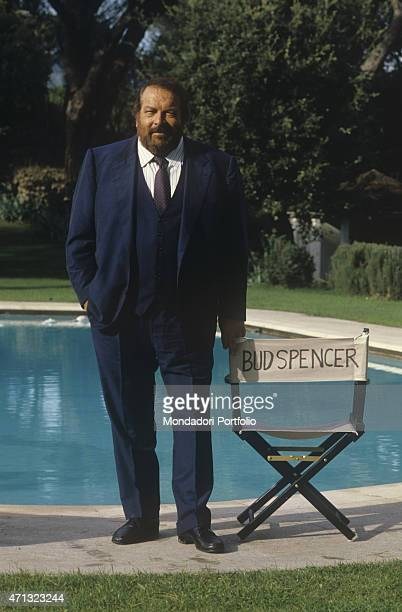 Italian actor Bud Spencer posing beside a folding chair bearing his name on the set of the TV series Big Man. 1987