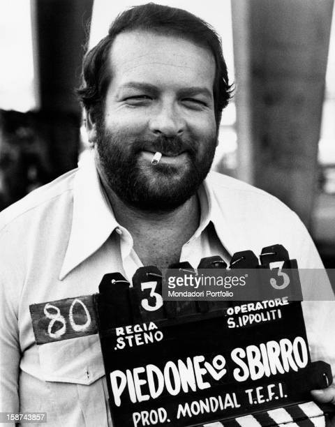 Italian actor Bud Spencer smoking a cigarette holding the clapperboard of the film The Knock Out Cop. Naples, 1973