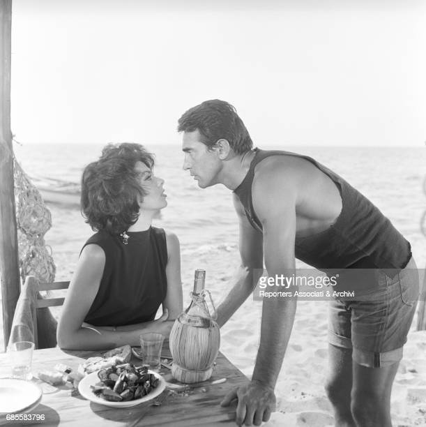 Italian actor comedian and TV host Walter Chiari playing the role of Bortolo a funny fisherman and Britishborn Italian actress Gloria Paul sitting at...