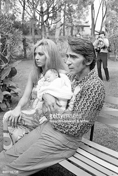 Italian actor comedian and TV host Walter Chiari sitting on a bench holding his newborn baby Simone in his arms Next to him his wife Italian actress...