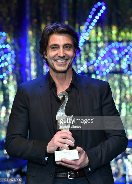 Italian actor Daniele Liotti poses with his award at theItalian film ball 'Notte delle Stelle' held during the 67th International Berlin Film...