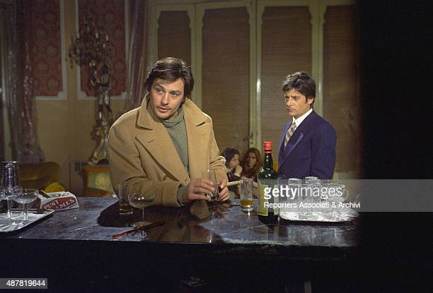 Italian actor director and scriptwriter Giancarlo Giannini watching French actor director and singer Alain Delon resting on the counter of a bar in...