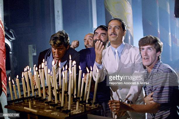 Italian actor director and singer Nino Manfredi and Italian actors Ugo Fangareggi Pinuccio Ardia Mario Adorf and Dante Maggio lighting candles in a...