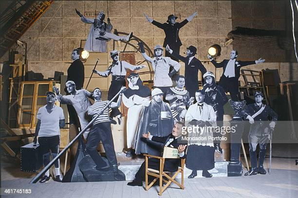 Italian actor, dubber and director Alberto Sordi sitting on a director's chair among the silhouettes depicting some of his characters, as the traffic...