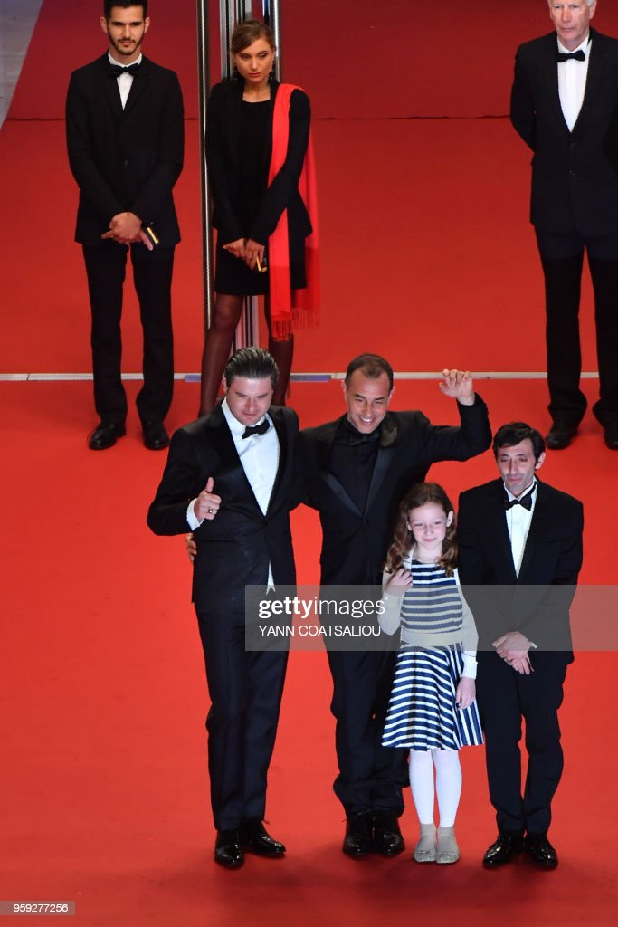 Italian actor Edoardo Pesce, Italian director Matteo Garrone, Italian actor Marcello Fonte and Italian actress Alida Baldari Calabria wave as they arrive on May 16, 2018 for the screening of the film 'Dogman' at the 71st edition of the Cannes Film Festival in Cannes, southern France.