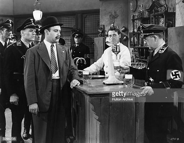 Italian actor Eduardo Ciannelli looks on while Lee J Cobb and Charles Arnt show a suspicion that the mixer on his bar is actually part of a radio...