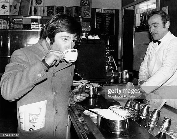 Italian actor Enzo Cerusico has breakfast in a bar with cappuccino and a brioche Rome 1974
